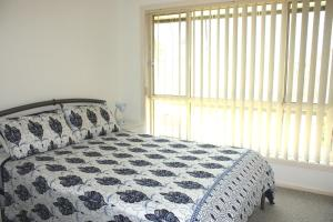 A bed or beds in a room at BEACH COMBER