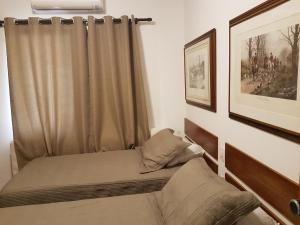 A bed or beds in a room at Flat Guarujá Capitania Varam