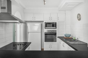 A kitchen or kitchenette at Beachfront Apartment with Balcony, Parking and Pools