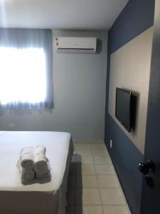 A television and/or entertainment center at Muro Alto Suites - Marupiara