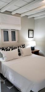 A bed or beds in a room at Pleiades Modern Apt With Shared Pool in Ornos!