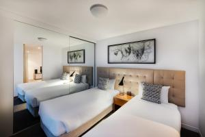 A bed or beds in a room at Peppers Broadbeach