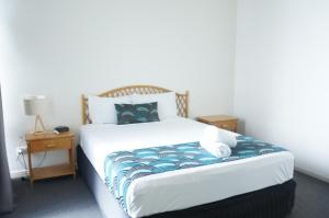 A bed or beds in a room at Airlie Whitsunday Terraces Resort