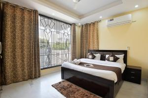 A bed or beds in a room at Olive Service Apartments Noida