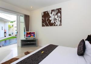 A bed or beds in a room at Awila Villas Kuta