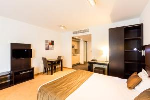 A television and/or entertainment centre at Diamant Suites Brussels EU