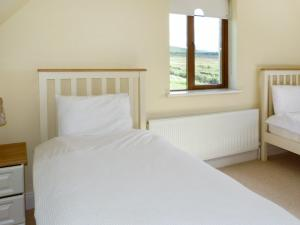 A bed or beds in a room at Ballycroy Bungalow
