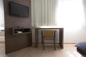 Uma TV ou centro de entretenimento em Flat Itaim Suites São Paulo