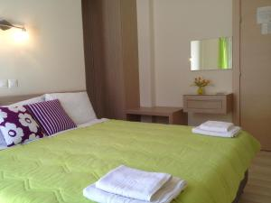 A bed or beds in a room at Angelica Studios and Apartments