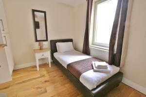 A bed or beds in a room at Central Studios Gloucester Road by RoomsBooked
