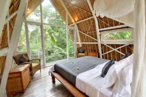 A bed or beds in a room at Jendela Di Bali Villa