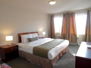 A bed or beds in a room at Beausejour Hotel Apartments/Hotel Dorval