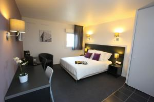 A bed or beds in a room at All Suites Orly-Rungis - Aéroport