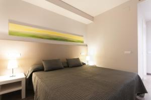 A bed or beds in a room at Espais Blaus Apartments