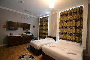A bed or beds in a room at Hyde Park Suites