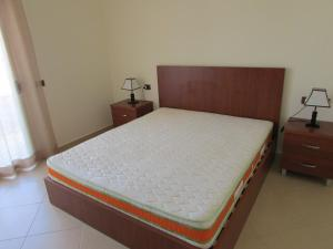 A bed or beds in a room at Aati Apartment