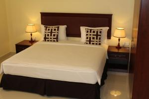 A bed or beds in a room at Nizwa Hotel Apartments