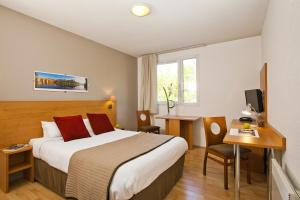 A bed or beds in a room at Séjours & Affaires Toulouse de Brienne