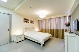 A bed or beds in a room at Dizengoff Inn Apartments