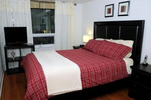 A bed or beds in a room at JJ Furnished Apartments Downtown Toronto: Entertainment District Element
