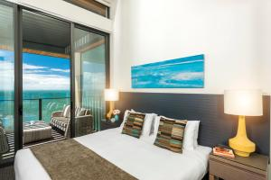 A bed or beds in a room at Oaks Redcliffe Mon Komo Suites