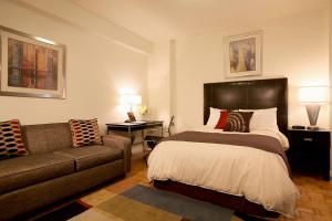 A bed or beds in a room at Oakwood Aurora Midtown East