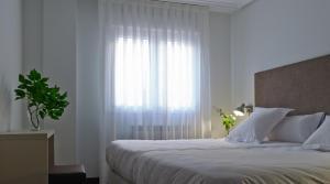 En eller flere senger på et rom på Apartamentos Turísticos Taranco 5