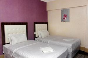Un ou plusieurs lits dans un hébergement de l'établissement Delmon Hotel Apartments