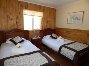 A bed or beds in a room at Cabañas Nutrias Patagonicas
