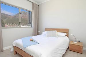 A bed or beds in a room at Royal Apartments Muizenberg