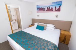 A bed or beds in a room at Beach Club Resort Mooloolaba