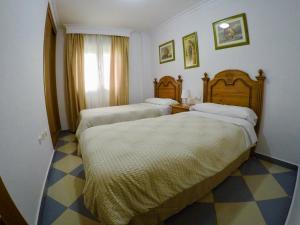 A bed or beds in a room at Apartamentos Niña de Oro