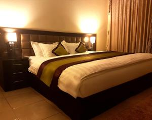 A bed or beds in a room at Qasr Al Aziqia Furnished Apartment