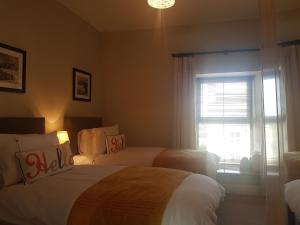 A bed or beds in a room at Heneghans Pharmacy Apartment