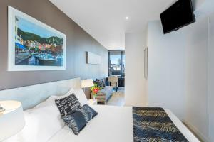 A bed or beds in a room at Aura on Flinders Serviced Apartments