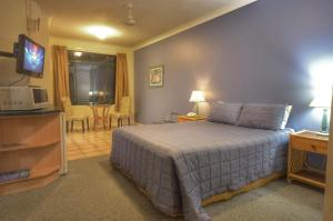 A bed or beds in a room at Grosvenor in Cairns