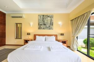 A bed or beds in a room at View Talay Pool Villa Pattaya