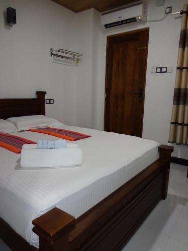 A bed or beds in a room at Rajarata Reach Resort