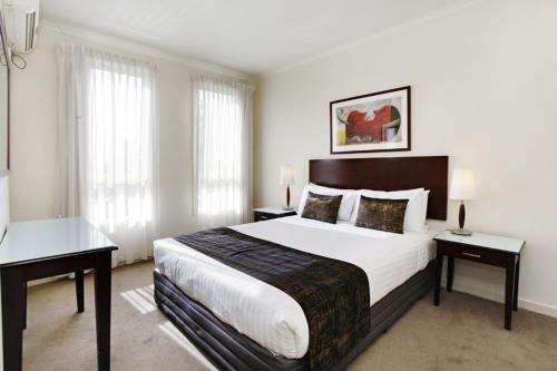 A bed or beds in a room at Quest Royal Gardens