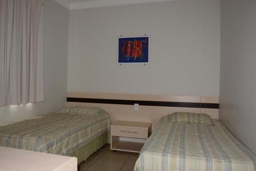 A bed or beds in a room at Aguas da Serra Apart Service