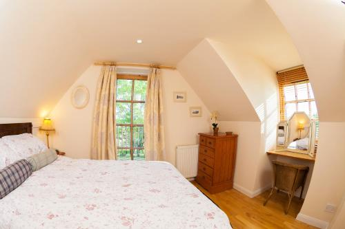 A bed or beds in a room at Flowers of May Cottage
