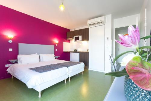 A bed or beds in a room at Néméa Appart'hotel Toulouse Constellation