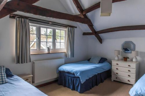 A bed or beds in a room at Cheristow Farm Cottages