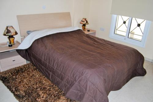 A bed or beds in a room at Mazotos Panoramic Village