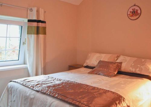 A bed or beds in a room at Ty Maen Cottage