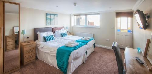 A bed or beds in a room at Shanklin Villa Apartments