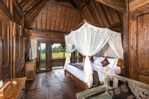 A bed or beds in a room at Kawan Antique Ubud Villa