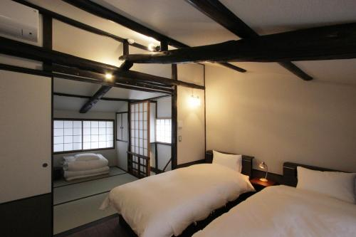 A bed or beds in a room at Momohana an Machiya House