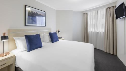 A bed or beds in a room at Oaks on Castlereagh, Sydney Central