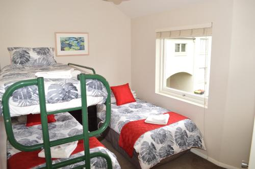 A bed or beds in a room at Akaroa Central Apartment